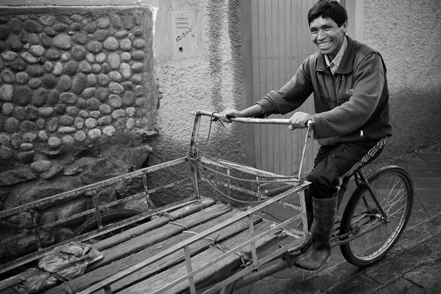Smiling man rides a bicycle cart